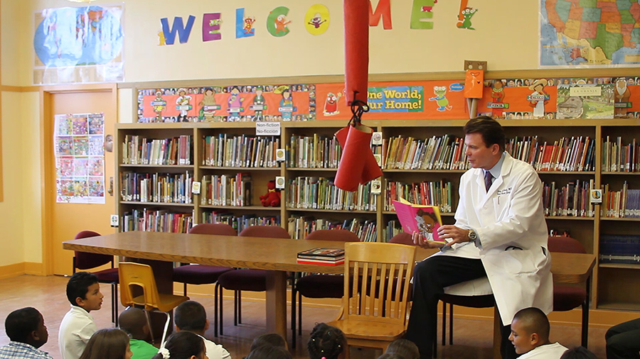 Dr. Corey Maas reads to children at a San Francisco Bay Area School.